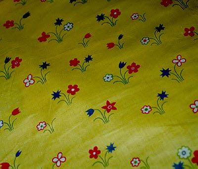 Rouleau de toile à fleurs stylisées sur fond jaune.