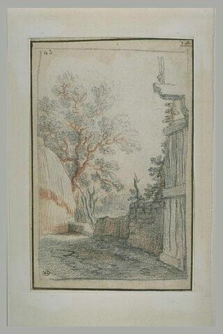Vue d'une ruelle de village avec une meule et un arbre