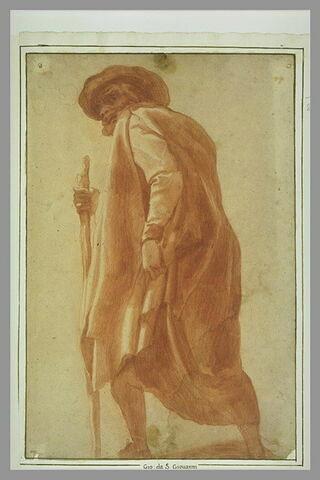 Homme drapé dans un manteau, coiffé d'un chapeau, appuyé sur un bâton et marchant vers la gauche
