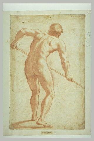 Homme nu, debout, vu de dos, tenant des deux mains un baton