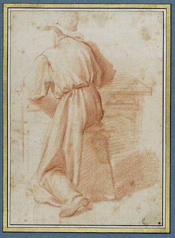 Homme vêtu d'une longue robe, coiffé d'un chapeau, assis à une table, vu de dos
