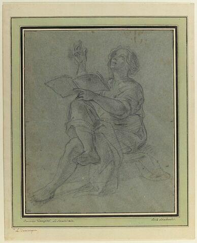 Jeune homme assis, jambes croisées, tenant un livre, les yeux levés