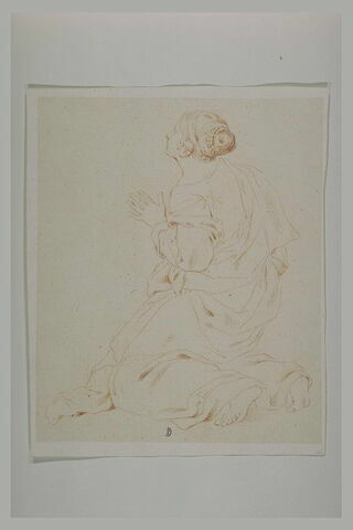 Une jeune femme à genoux, la maingauche tendue