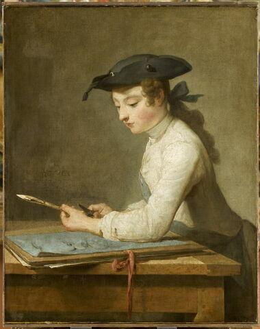 Jeune dessinateur taillant son crayon.