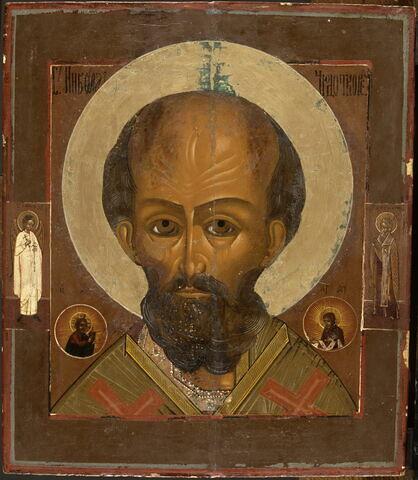 Saint Nicolas thaumaturge, encadré de deux médaillons contenant les figures du Christ (à gauche) et de la Vierge (à droite) ; sur les bords,à mi-auteur, en pied, l'Ange gardien (à gauche) et le saint évêque Euthyme (à droite).