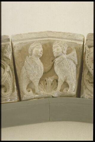 Deux basilics (?) à tête humaine, de part et d'autre d'une palmette