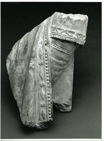 Fragment de main droite gantée et d'avant bras recouvert d'une draperie ornée d'un galon