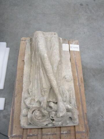 Paire de jambes dont les pieds reposent sur des feuillages