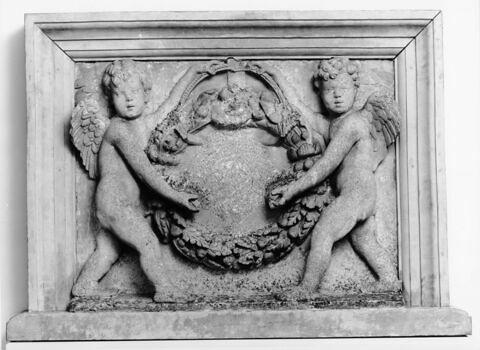Deux angelots portant un écusson martelé à la Révolution