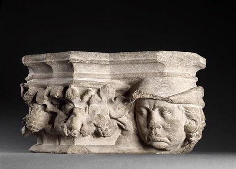 Chapiteau décoré d'une tête d'homme coiffé d'un bonnet, de feuilles de vigne et de grappes de raisin