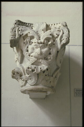 Chapiteau décoré de rinceaux de perles, de feuillages et d'une tête de lion ou de monstre