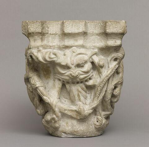 Chapiteau décoré de rinceaux perlés, de feuillages et d'une tête de lion ou de monstre