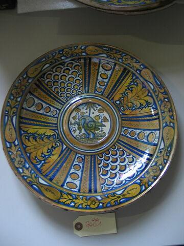 Bassin d'aiguière.Au centre, dans un médaillon, un oiseau. Décor rayonnant. Faïence Deruta, 1er quart XVIème siècle.
