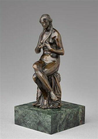 Statuette : femme se tressant les cheveux