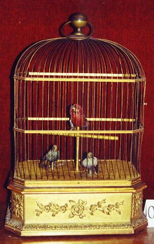 Petite cage enfermant trois oiseaux chanteurs