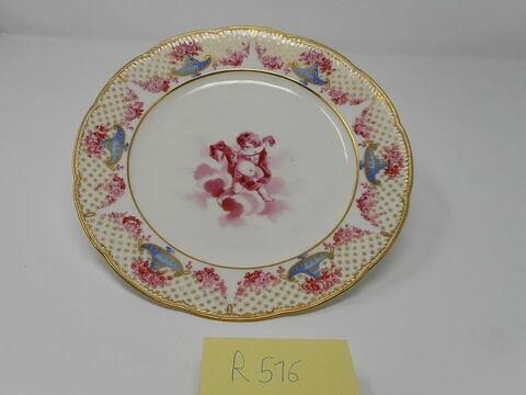 Assiette d'une série de quarante et une (R 510 à 549 bis); du service en pâte tendre blanche décorée de vases fleuris et d'amour en camaïeu rose et à bordure oeil de perdrix doré (R 489 à 549)