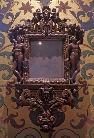 Miroir en glace métallique, dans un cadre en bois sculpté et doré