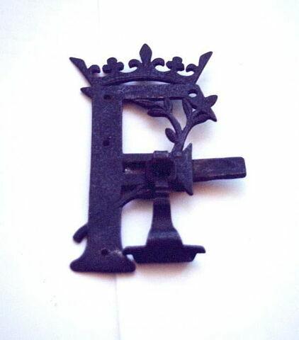 Targette en forme de F couronné, pendeloque en forme de feuille.