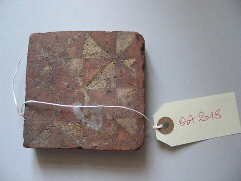 Carreau : damier formé de losanges blancs sur rouge. Terre vernissée. France, XIVème siècle.