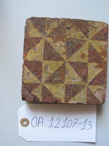 Carreau : damier formé de losanges blancs sur rouge. Terre vernissée. France, XIII-XIVème siècle. H 0,025 ; côté 0,120.