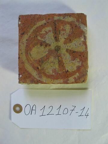 Carreau : rosace à six pétales. Terre vernissée ocre et jaune ; traces de glaçure. France, XIIIème , XIVème siècle. H 0,02 ; côté 0,10.