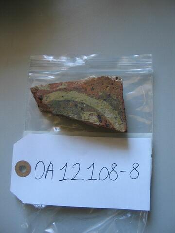Fragment de carreau : fleur de lis (?) inscrite dans une cercle. Terre vernissée ocre et jaune. H : 0,02 ; L : 0,08 ; l : 0,05
