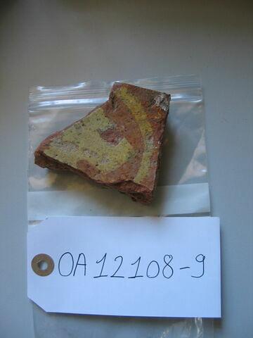 Fragment de carreau : fleur de lis (?). Terre cuite ocre et jaune ; traces de glaçure. H : 0,02 ; L : 0,08 ; l : 0,07