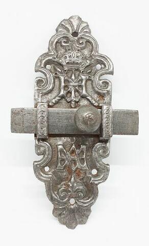 Verrou en métal repoussé de forme oblongue, décoré d'une coquille à la partie supérieure et à la partie inférieure