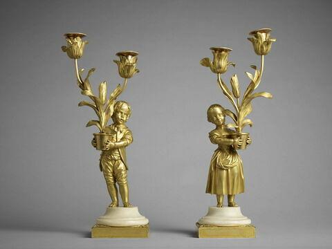 Petit candélabre à deux lumières d'une paire petit garçon tenant des fleurs
