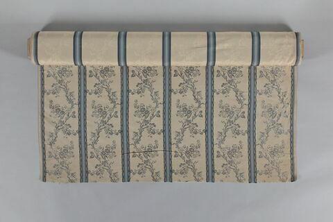 Lampas moiré décoré de feuillages en bandes séparés par cinq bandes verticales bleues. Style Louis XVI.