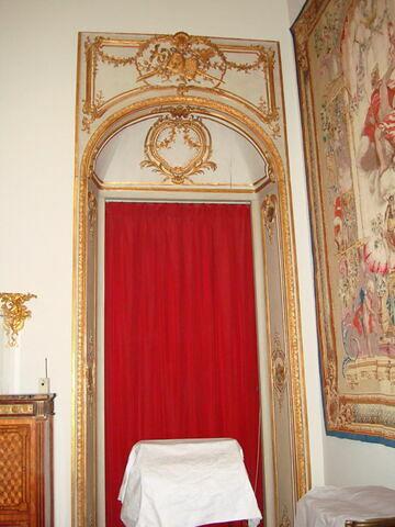 Porte surmontée d'un trophée avec un caducée et un pell.