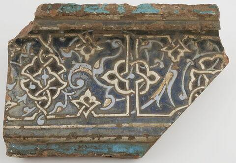 Fragment d'une corniche à inscription kufique noué
