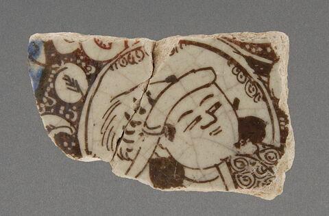 fragment de carreau au personnage coiffé de plumes de hiboux