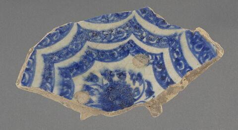 """Moitié de fond d'une grande coupe à décor concentrique de """"rubans"""" bleu et blanc"""