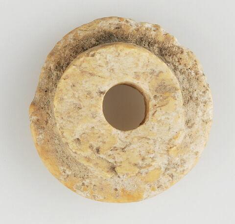Élément circulaire perforé (partie supérieure d'élément de préhension ?)