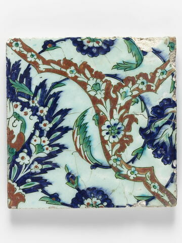 Carreau à décor de médaillons formés d'arabesques florales, de palmettes feuillues et de fleurs composites