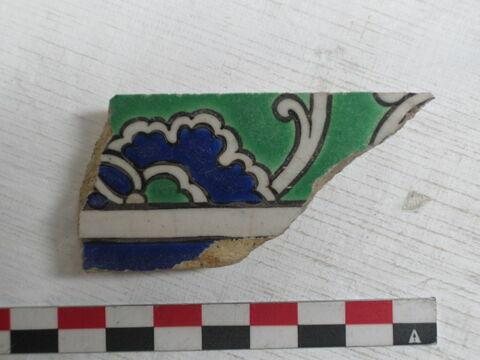 Fragment d'un carreau de bordure au rinceau de rumi enfermant des fleurettes et des pivoines