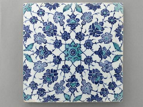Carreau à arabesque fleurie partant d'une étoile et d'un motif central à appendices fleuronnés