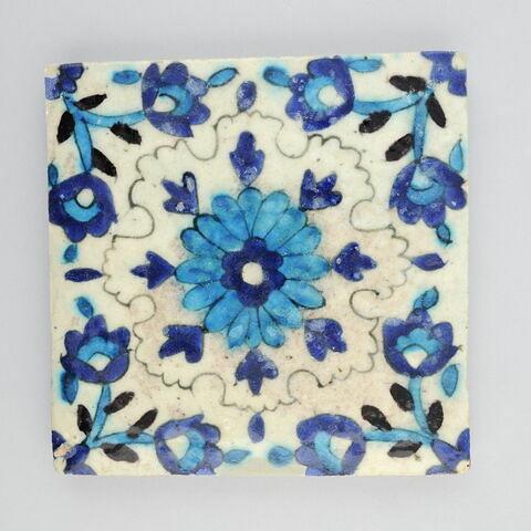 Carreau à large fleur centrale et tiges fleuries dans les angles