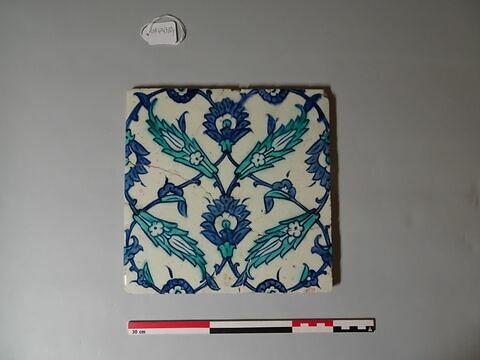 Carreau à décor floral bleu et blanc organisé en réseau losangé