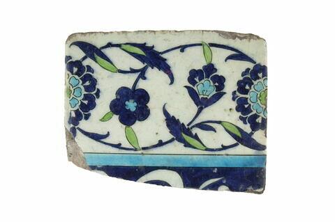 Carreau de bordure fragmentaire à inscription (?) sur fond bleu sombre. Bordure à rinceaux fleuris de rosettes et fleurettes