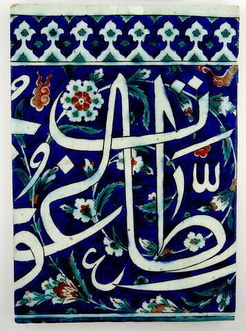 Carreau à inscription sur fond bleu fleuri