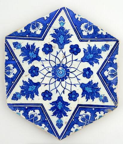 Carreau à l'étoile décoré d'un motif fleuri rayonnant à partir d'une rosette et d'une rosace
