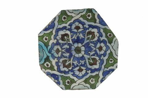 Carreau octogonal à motif étoilé contenant un motif floral centré