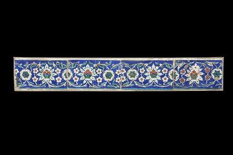 Carreaux de bordure aux lotus alternant avec des fleurettes et des rosettes sur fond bleu
