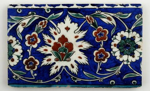 Carreau de bordure aux lotus alternant avec des fleurettes et des rosettes sur fond bleu