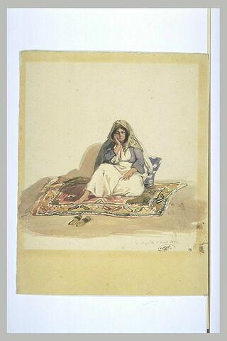 Femme syrienne assise sur un tapis d'Orient et sur un coussin bleu à fleurs