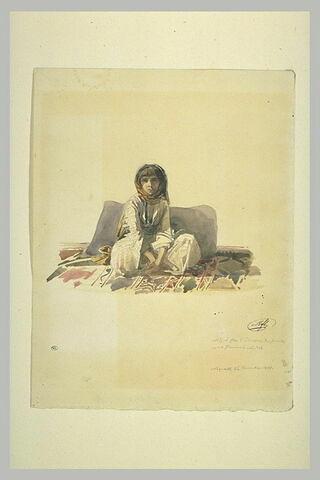 Jeune fille de Palestine accroupie sur un tapis d'Orient devant des coussins