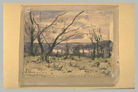 Vue d'un village depuis une colline boisée, en hiver