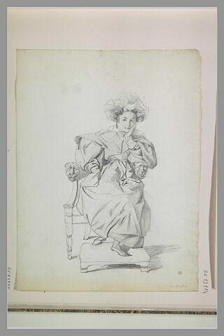 Femme assise sur un fauteuil, les pieds sur un tabouret